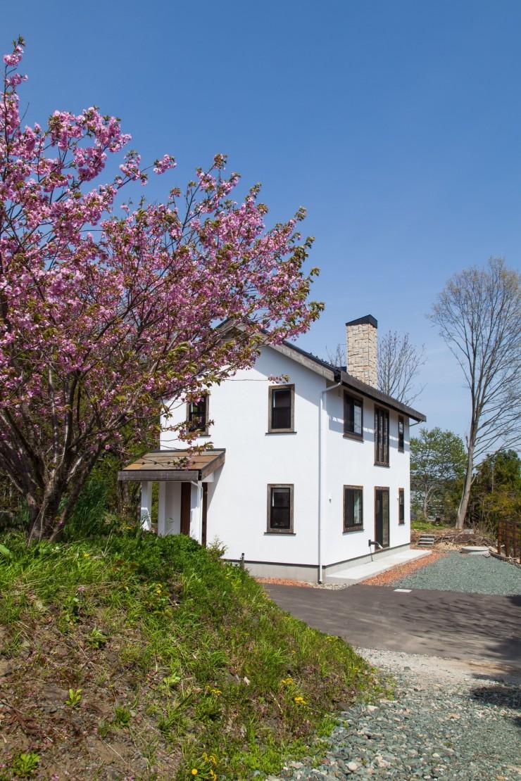 花をつけた木立からのぞく、漆喰壁と煙突が印象的な無添加住宅